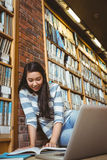 Smiling student sitting on the floor against wall in library studying with laptop and books Stock Images