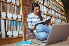 Smiling student sitting on the floor against wall in library studying with laptop and books Stock Photo
