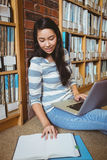 Smiling student sitting on the floor against wall in library studying with laptop and books Stock Image