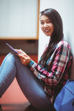 Smiling student sitting on the floor and using tablet Stock Photo