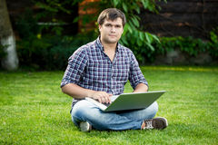 Smiling student sitting on grass at park and typing on laptop Stock Photography