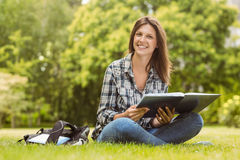 Smiling student sitting and holding a book Stock Photo