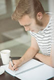 Smiling student sitting with a hot drink and writing on notepad Royalty Free Stock Photos