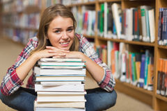Smiling student sitting on library floor leaning on pile of books