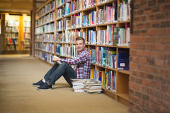 Smiling student sitting on library floor reading Stock Images
