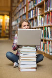 Smiling student sitting on library floor using laptop on pile of books Royalty Free Stock Photo