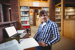 Smiling student sitting in library. Portrait of smiling student sitting in library at college Stock Photography