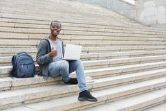 Smiling student sitting on stairs using laptop. Smiling african-american student with thumb up sitting on stairs working with laptop, preparing for exams Royalty Free Stock Photos