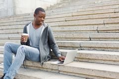 Smiling student sitting on stairs using laptop. Smiling african-american student sitting on stairs, working with laptop and having coffee, preparing for exams Royalty Free Stock Image