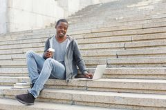 Smiling student sitting on stairs using laptop. Smiling african-american student sitting on stairs, working with laptop and having coffee, preparing for exams Royalty Free Stock Photos