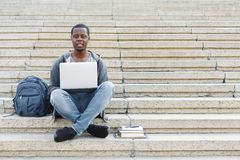 Smiling student sitting on stairs using laptop. Smiling african-american student sitting on stairs working with laptop, preparing for exams outdoors, having rest Stock Images