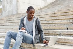 Smiling student sitting on stairs using laptop. Smiling african-american student sitting on stairs, working with laptop and taking notes, preparing for exams Stock Image