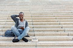 Smiling student sitting on stairs using tablet. Smiling african-american student sitting on stairs working with digital tablet, preparing for exams outdoors Stock Images