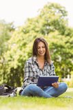 Smiling student sitting and using tablet pc Stock Image
