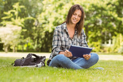 Smiling student sitting and using tablet pc Stock Photography