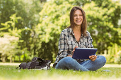 Smiling student sitting and using tablet pc Royalty Free Stock Photography