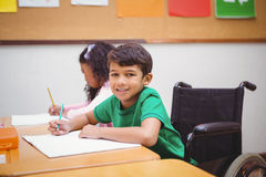 Smiling student sitting in wheelchair Stock Images