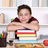 Smiling student on a stack of books at school Royalty Free Stock Images