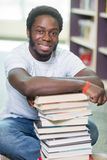 Smiling Student With Stacked Books Sitting In. Full length portrait of smiling male student with stacked books sitting on floor at library Royalty Free Stock Photos