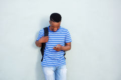 Smiling student standing against wall with bag and mobile phone. Portrait of smiling african student standing against wall with bag and mobile phone Royalty Free Stock Photography