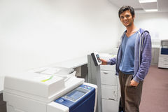 Smiling student standing next to the photocopier Stock Photos