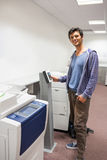 Smiling student standing next to the photocopier Royalty Free Stock Photo