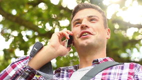 Smiling student standing outside talking on the phone stock video footage