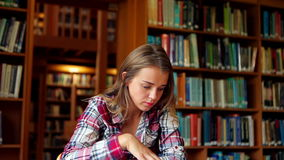 Smiling student studying at desk in the library stock footage