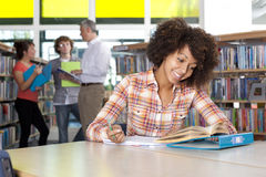 Smiling student studying in school library Stock Photos