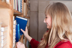 Smiling student taking a book Stock Image