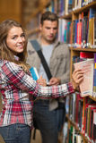 Smiling student taking book from shelf in library Stock Images