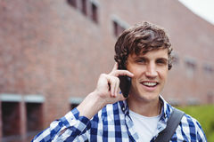 Smiling student talking on mobile phone Royalty Free Stock Image