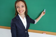Smiling student or teacher standing in front of the blank  blackboard with piece of chalk in her hand. Stock Photos