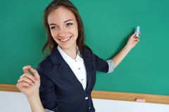 Smiling student or teacher standing in front of the blank  blackboard with piece of chalk in her hand. Stock Image