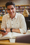 Smiling student using his smartphone. In library Stock Images
