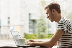 Smiling student using laptop in cafe Stock Photography