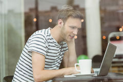 Smiling student using laptop in cafe. At the university Stock Photography