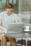 Smiling student using laptop in cafe Royalty Free Stock Photos