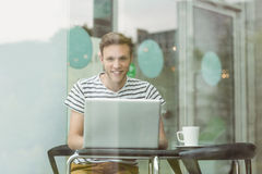Smiling student using laptop in cafe Stock Image