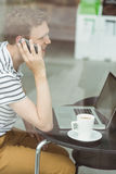 Smiling student using laptop and smartphone in cafe Royalty Free Stock Photography