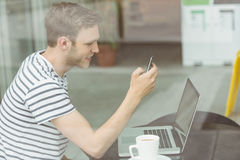 Smiling student using laptop and smartphone in cafe Stock Images