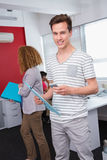 Smiling student using smartphone near classmates. At the college Stock Photo