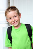 Smiling student wearing backpack. A young boy smiles before going to school. He is wearing a backpack Stock Images