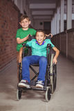 Smiling student in a wheelchair and friend beside him Royalty Free Stock Photography