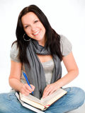 Smiling student woman making notes in Royalty Free Stock Photos