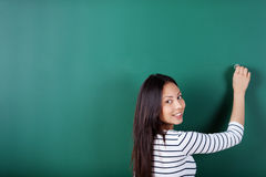Smiling student writing on empty blackboard Stock Images