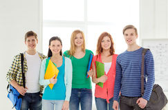 Smiling students with bags and folders at school Stock Photos