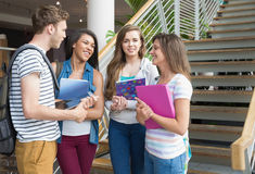 Smiling students chatting together outside Royalty Free Stock Photos