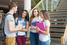 Smiling students chatting together outside Stock Photo