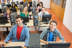 Smiling students in the college computer room Royalty Free Stock Images
